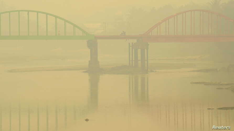 A resident rides a motorcycle on the haze-shrouded Betrix bridge in Sarolangun, on Indonesia's Jambi province, Oct. 7, 2015