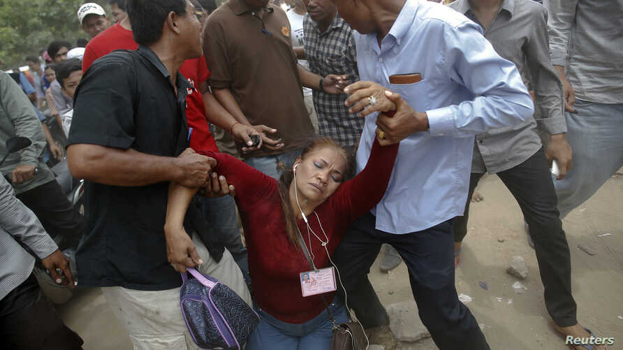 FILE - An election committee official, who has lost consciousness, is helped out of a polling station after an angry mob surrounded her in a protest against alleged election irregularities in Phnom Penh, July 28, 2013.