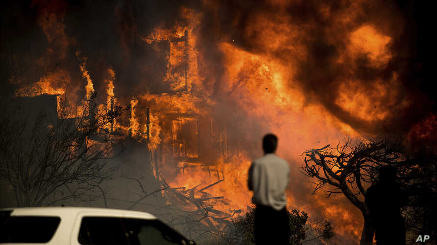 A man watches flames consume a residence as a wildfire rages in Ventura, Calif., Dec. 5, 2017.