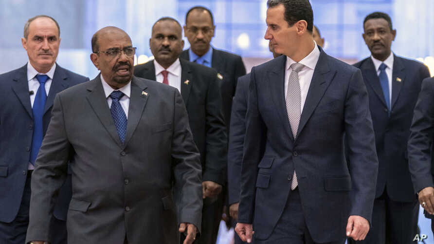 FILE - In this photo released by the Syrian official news agency SANA, Syrian President Bashar al-Assad, right, meets with Sudan's President Omar al-Bashir in Damascus, Syria, Dec. 16, 2018.