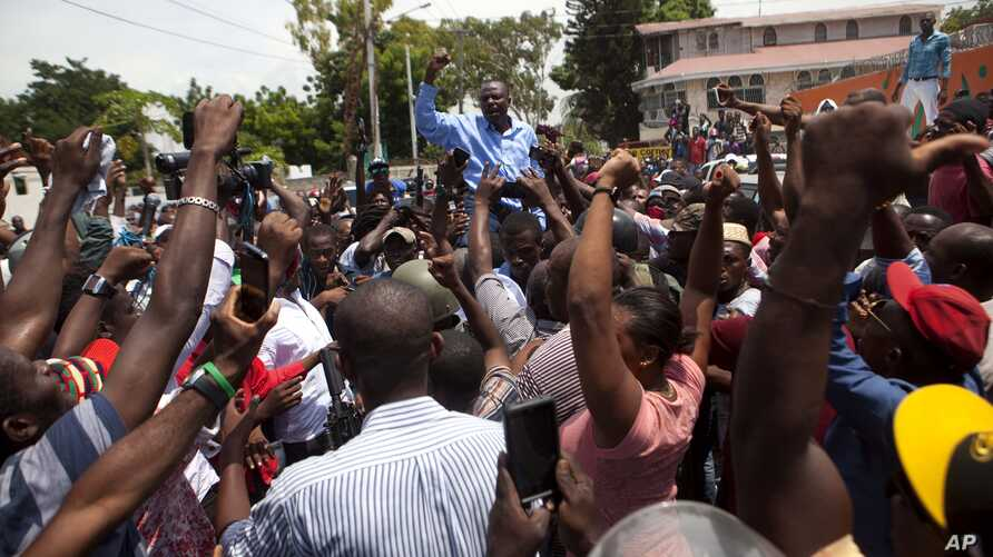 Former Presidential candidate Moise Jean-Charles from the Platform Pitit Dessalines party, is carried by supporters after national police officers attempted to detain him in Delmas, a district of Port-au-Prince, Haiti, Sept. 13, 2017.