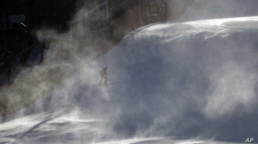 A course worker is shrouded in snow as it blows across the course where the technical events will be held before an inspection by competitors in the women's giant slalom at the Yongpyong Alpine Center at the 2018 Winter Olympics in Pyeongchang, South