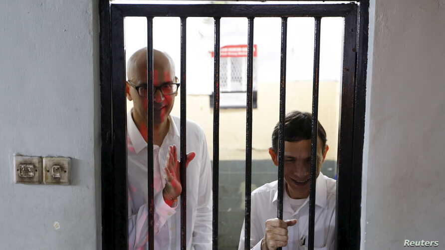 FILE - Canadian teacher Neil Bantleman (L) waves beside Indonesian teaching assistant Ferdinand Tjiong to students as they wait inside a holding cell before their trial at a South Jakarta court, Indonesia, April 2, 2015.