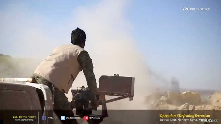 A Kurdish fighter fires a weapon at Islamic State held territory in Baghouz, eastern Syria in this still image taken from a video published March 4, 2019 by the YPG Press Office.