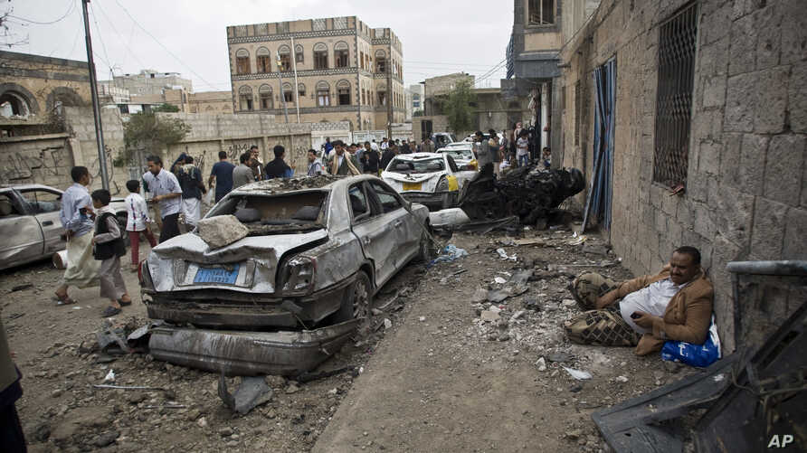 A man rests next to his car destroyed by Saudi-led airstrikes in Sanaa, Yemen, May 27, 2015.