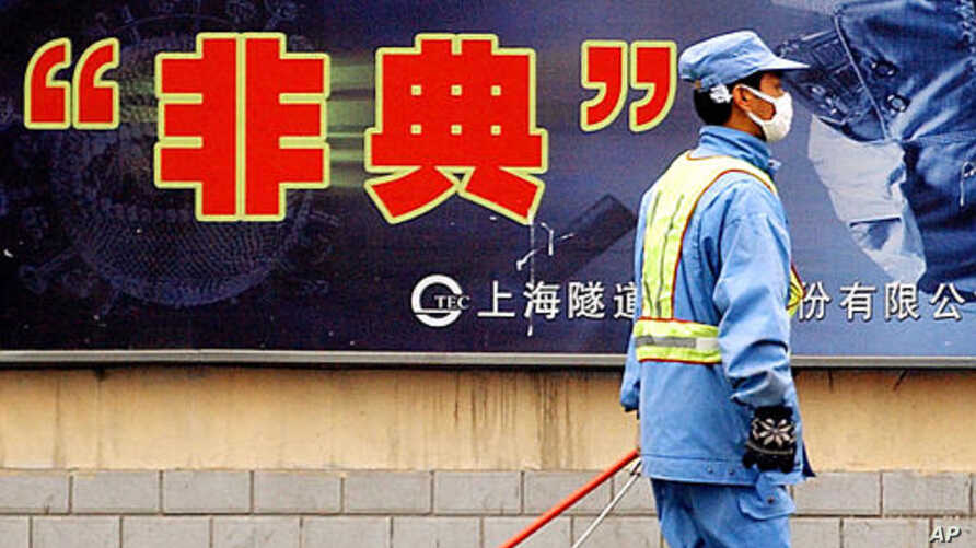 City employee wearing protective mask walks past local government anti-SARS advertisement, Shanghai, Dec. 29, 2003.