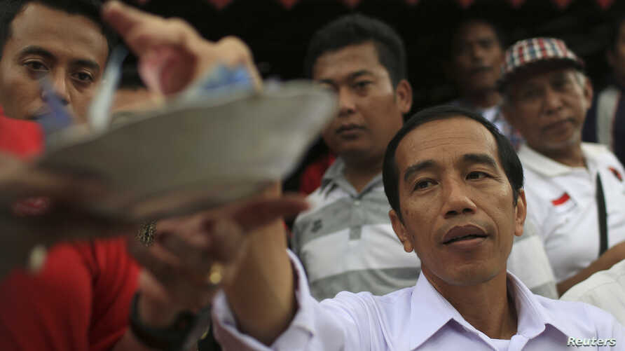 Jakarta governor and presidential candidate Joko Widodo gives donation during lunch with his supporters from the PDI-P party in Jakarta March 16, 2014. In a sign Indonesians are coming to assume that the hugely popular Jakarta governor Joko Widodo wi