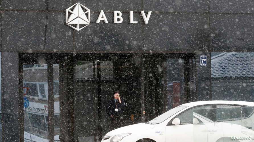 A security guard speaks on her mobile phone at the head office of the ABLV Bank in Riga, Latvia Feb. 18, 2018.