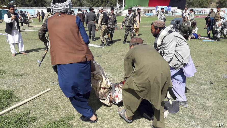 A wounded man is carried away following explosions at an agrucultural show in Lashkar Gah, Helmand province, southern Afghanistan, March 23, 2019.