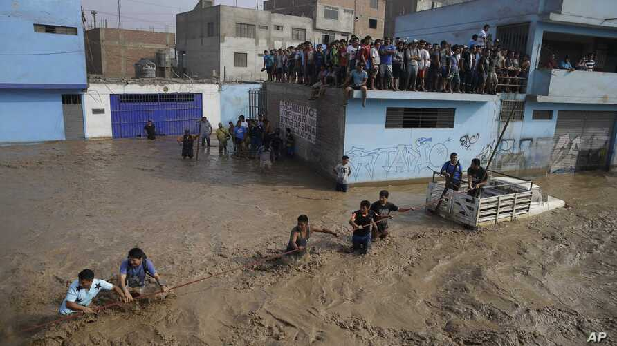 A group of people, stranded in flood waters, hold onto a rope as they walk to safety in Lima, Peru, March 17, 2017. Intense rains and mudslides recently have wrought havoc around the Andean nation and caught residents in Lima, a desert city of 10 mil...