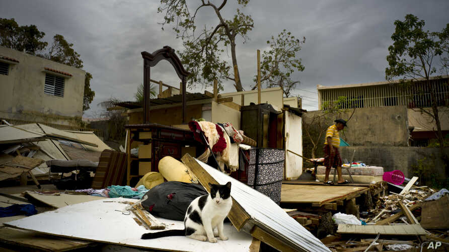 Efrain Diaz Figueroa, right, walks by his sister's home destroyed in the passing of Hurricane Maria, in San Juan, Puerto Rico, Monday, Oct. 9, 2017.