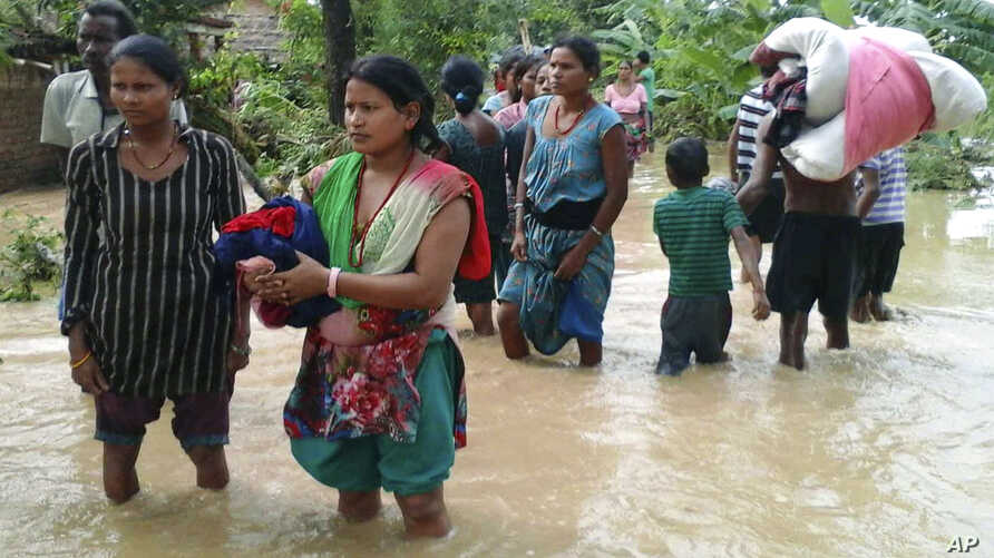 Nepalese villagers carry their belongings while wading through a flooded street to move to safer ground, at Bardia, in western Nepal., Aug. 15, 2014.