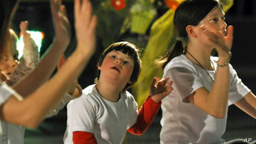 A child with Down's syndrome (C) participates in a performance during a humanitarian concert for children with Down's syndrome, (File)