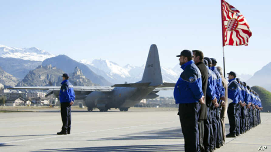 Police officers pay tribute to the 28 victims of the bus crash in Sierre, as they stand next to a Belgian military cargo aircraft, which is headed for Belgium, at Sion airport in western Switzerland March 16, 2012.