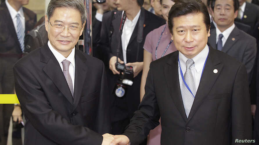 Zhang Zhijun (L), director of China's Taiwan Affairs Office, shakes hands with Mainland Affairs Council Vice Minister Chang Hsien-yao, after arriving at Taoyuan International Airport, northern Taiwan, June 25, 2014.