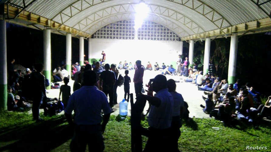 Central Americans are seen in the town of Tantima, Mexico, after Mexican authorities said that they rescued 147 Central Americans abandoned in the wilderness of Veracruz state, in this handout photograph released by Mexican National Institute of Migr
