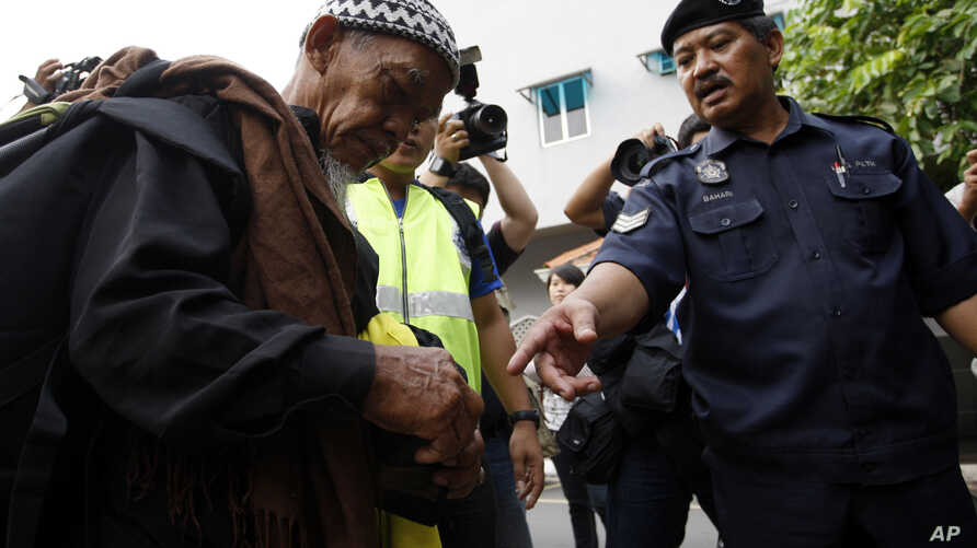FILE - a police officer checks a man's identity in Kuala Lumpur, Malaysia.