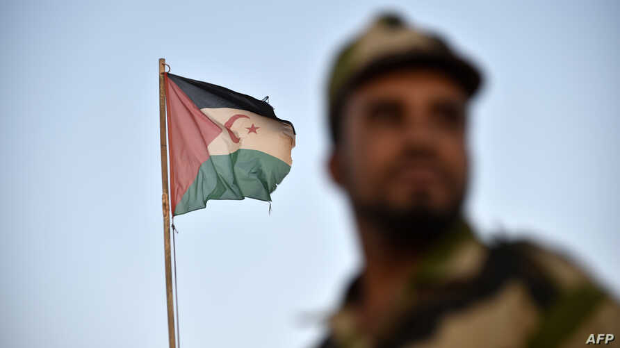 Uniformed soldiers of the pro-independence Polisario Front stand before a Sahrawi flag flying at the Boujdour refugee camp near the town of Tindouf in Western Algeria on Oct.17, 2017.