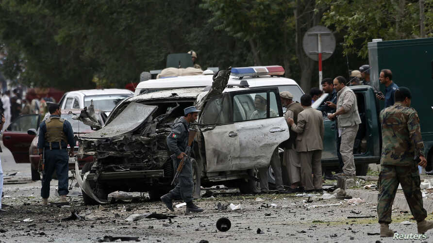 Afghan policemen investigate the site of a suicide attack in Kabul, June 6, 2014.