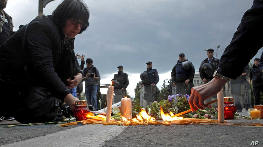 People light candles and lay flowers as police officers stand guard in front of the Government building in Skopje, Macedonia, May 11, 2015.