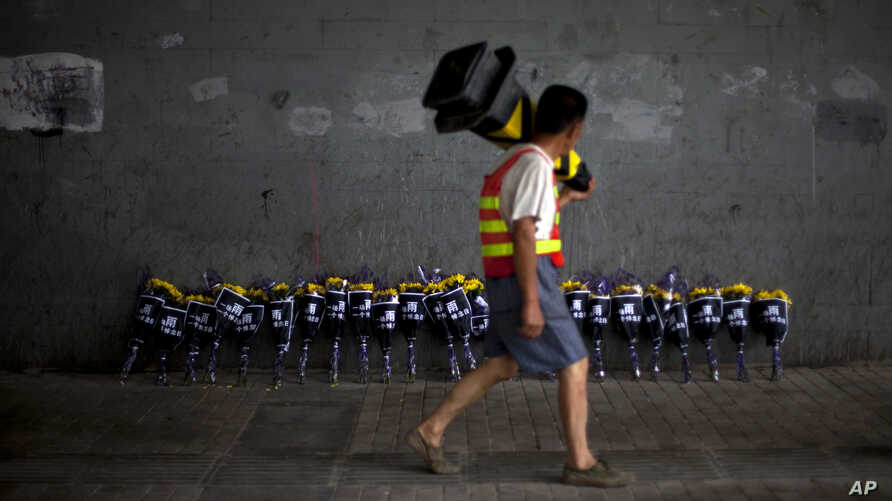 A road worker walks past flowers placed under a bridge where a man drowned July 21 in his flooded car on a main road in Beijing, July 27, 2012.