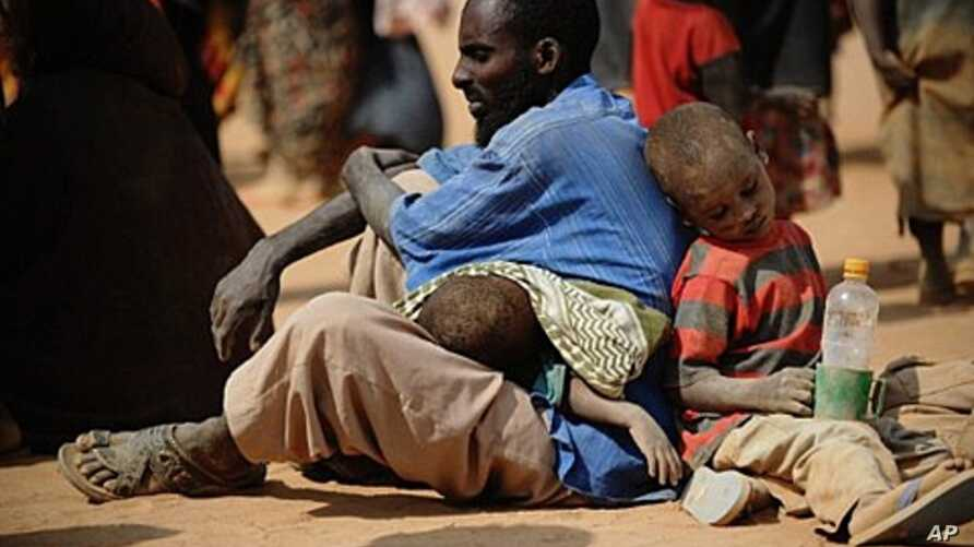 A Somali man who fled violence and drought in Somalia with his family sits on the ground outside a food distribution point in the Dadaab refugee camp in northeastern Kenya on July 5, 2011