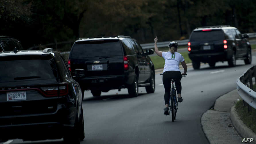 This file photo taken on October 28, 2017 shows a woman on a bike gestures with her middle finger as a motorcade with U.S. President Donald Trump departs Trump National Golf Course in Sterling, Virginia.