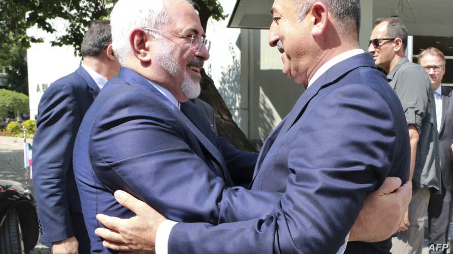 Turkish Foreign Minister Mevlut Cavusoglu (R) welcomes his Iranian counterpart Mohammad Javad Zarif (L) for a meeting at the Foreign Ministry in Ankara on August 12, 2016.