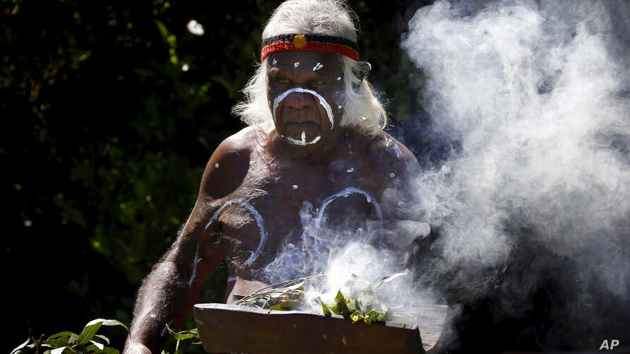 FILE - An aboriginal elder performs a ceremony during an official function at Sydney Harbor, Australia, Nov. 27, 2013. A new map documents massacres of aboriginees folllwing the arrival in Australia of British colonists in the late 18th century.