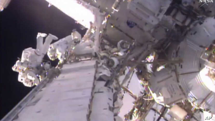 This image taken from video provided by NASA shows U.S. astronaut Shane Kimbrough (L), and  French astronaut Thomas Pesquet during a space walk outside the International Space Station, Jan. 13, 2017.