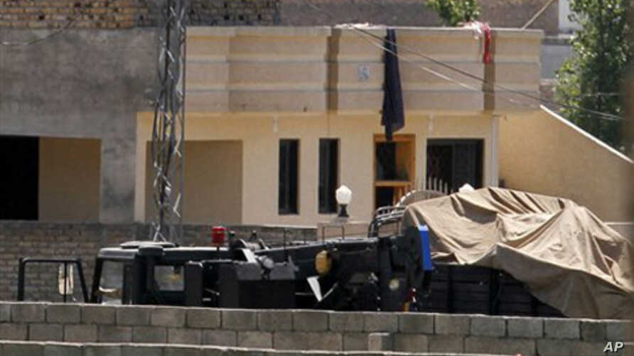 Vehicles are parked inside the compound of a house where it is believed al-Qaida leader Osama bin Laden lived in Abbottabad, Pakistan on Monday, May 2, 2011.