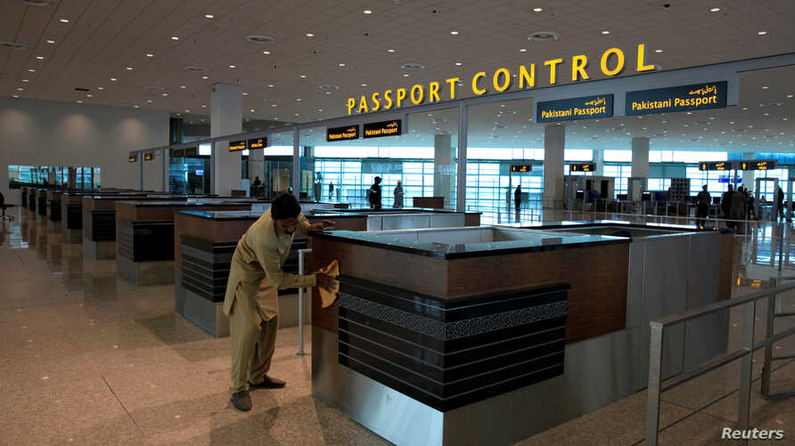 A worker cleans a passport control counter at Islamabad International Airport, in Islamabad, Pakistan, April 18, 2018.