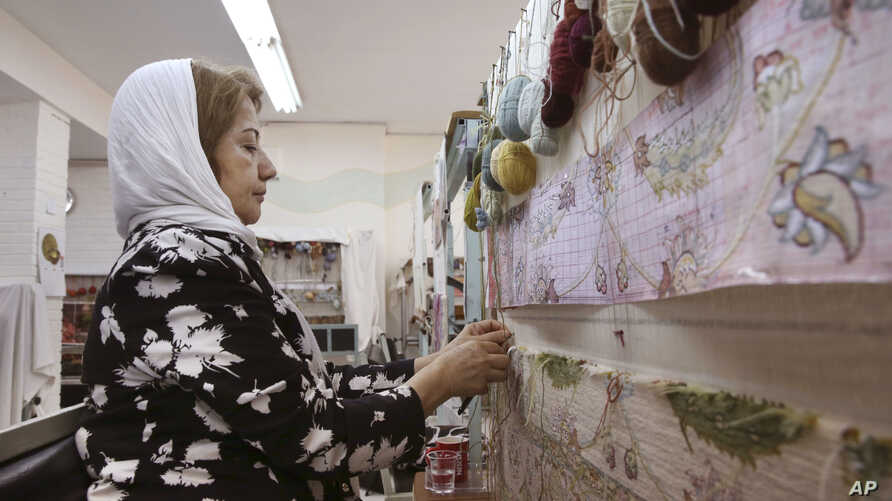An Iranian woman weaves a carpet at a workshop by the Cultural and Artistic Carpet Foundation of Rassam Arabzadeh in Tehran, Iran, Aug. 4, 2015.