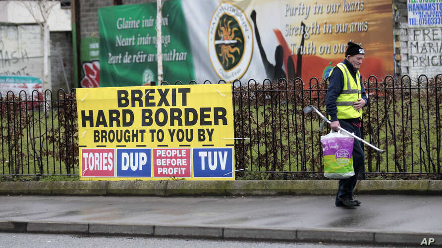 A man walks past republican posters referring to Brexit in West Belfast, Northern Ireland, Feb. 28, 2017.