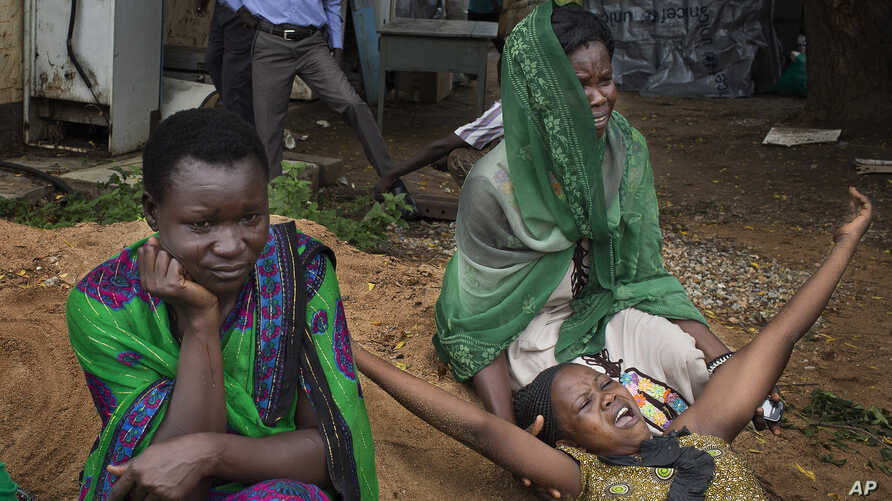FILE -  relatives of Samual Moro, 30, grieve after he died of cholera, outside the cholera isolation ward at the Juba Teaching Hospital in the capital Juba, South Sudan.