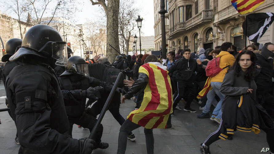Catalan police officers clash with demonstrators outside a subway after blocking a train rail, during a general strike in Catalonia, Spain, Feb. 21, 2019.