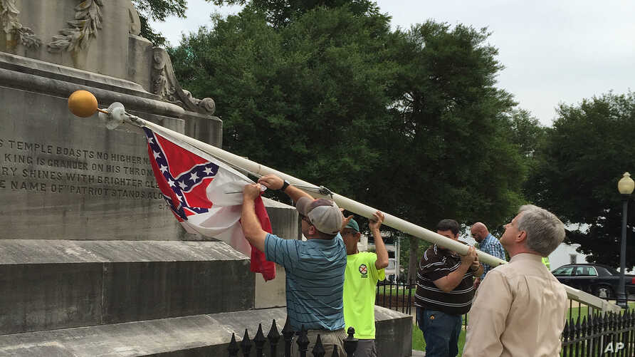 Alabama state workers take down a Confederate flag on the grounds of the state capitol in Montgomery, Alabama, June 24, 2015.