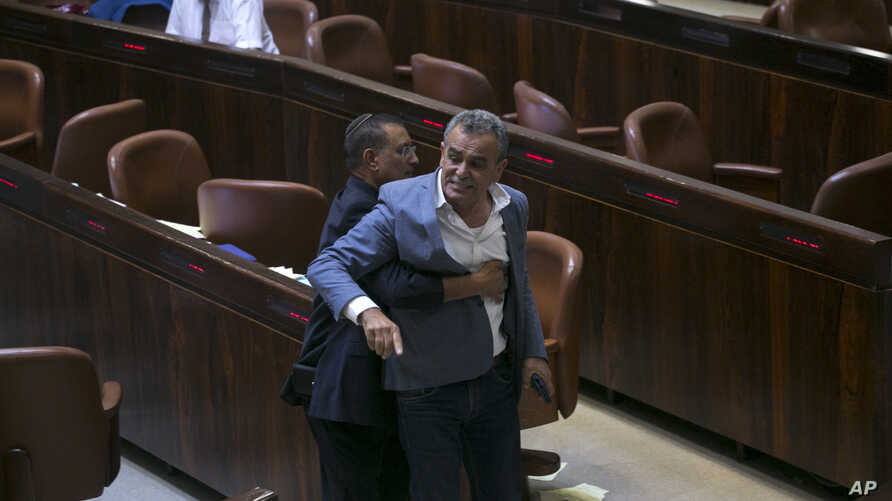 A Knesset usher removes Jamal Zahalka, an Israeli Arab member of the Knesset representing the Balad party, who was protesting the passage of a contentious bill, during a Knesset session in Jerusalem, Thursday, July 19, 2018. Israel's parliament appro