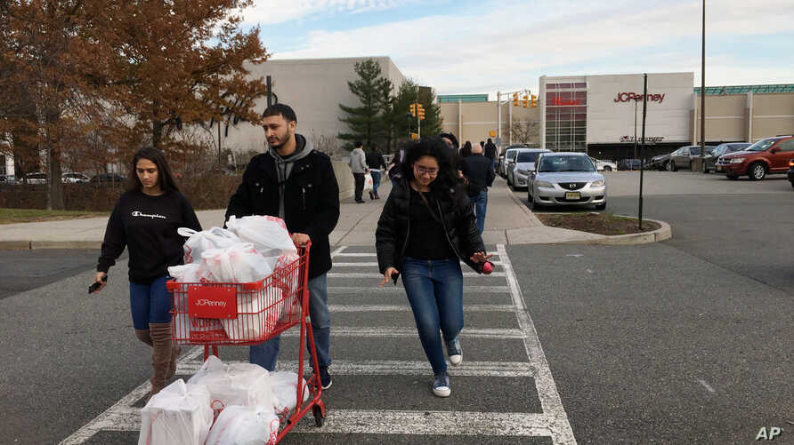 Shoppers walk back to their cars at the Garden State Plaza, in Paramus, New Jersey, Nov. 25, 2017.
