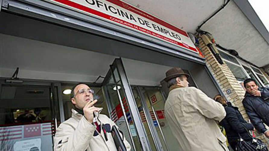 Unemployed factory worker Alejandro Jimenez, 35, left, smokes as he waits outside a government employment office for his turn to be attended in Madrid, 04 Jan, 2011