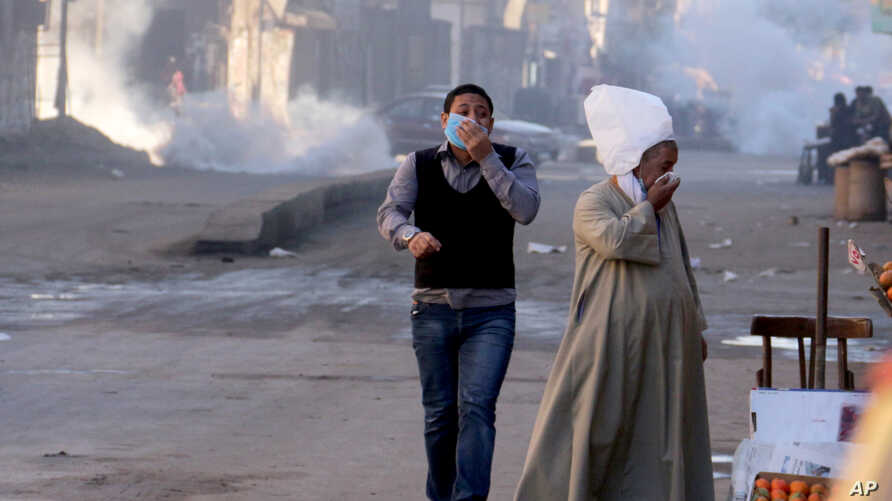 Egyptians react to tear gas fired by security forces to disperse a protest by supporters of ousted President Mohammed Morsi demanding his reinstatement, in Cairo, Egypt, Dec. 6, 2013.