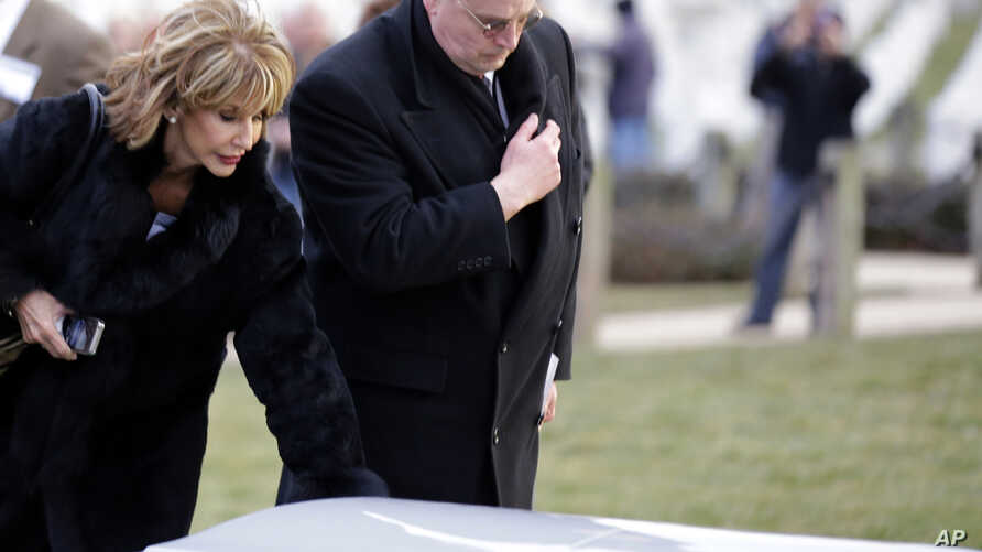 Diana Rambo her husband  pause at a casket of unidentified remains after services to honor two sailors from the USS Monitor, at Arlington National Cemetery, March 8, 2013 in Arlington. Mrs. Rambo is related to USS Monitor crew member Jacob Nicklis.