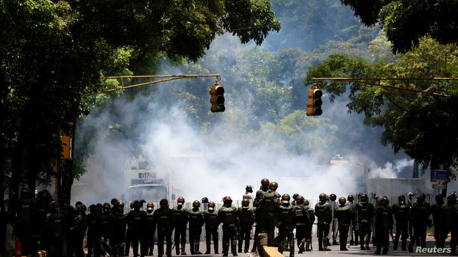 Riot police take position while clashing with opposition supporters during a rally against President Nicolas Maduro in Caracas, Venezuela, May 4, 2017.