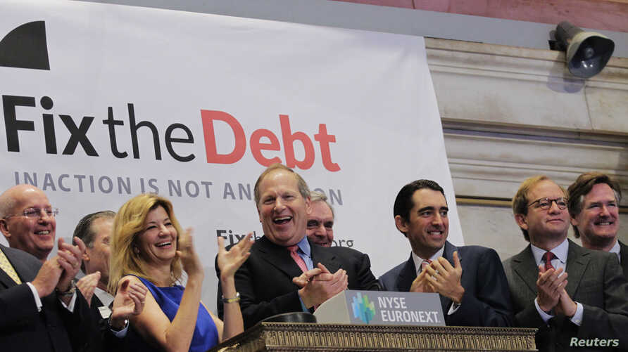 Maya MacGuineas, president of the Committee for a Responsible Federal Budget, and David Cote, (C) CEO of Honeywell international and part of the steering committee of the Campaign to Fix the Debt, are joined by supporters to ring the opening bell at