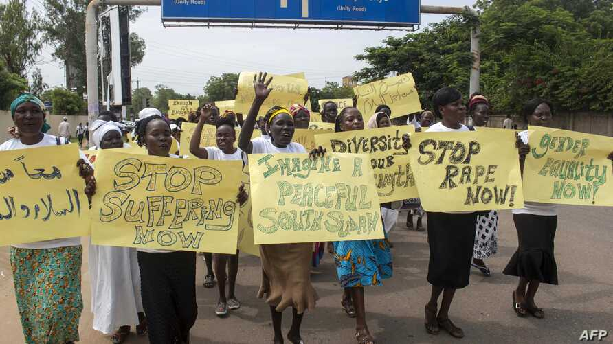 Women march carrying placards with messages demanding peace and their rights, on the streets of South Sudan's capital, Juba on July 13, 2018.
