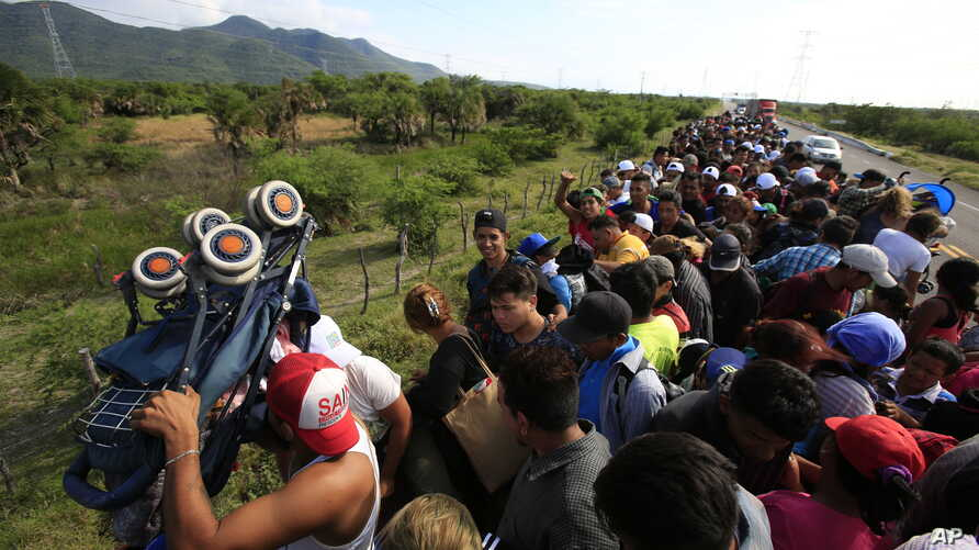 A man holds up a stroller as hundreds of migrants hitching a ride accommodate themselves on the back of truck, between Niltepec and Juchitan, Mexico, Oct. 30, 2018.