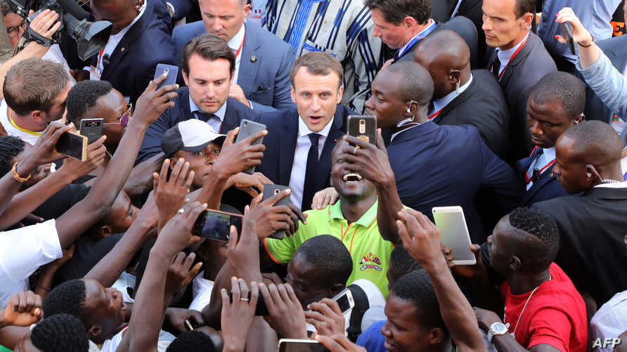 French President Emmanuel Macron (C) meets residents as he leaves the Ouagadougou University after giving a speech, Nov. 28, 2017, in Ouagadougou, as part of his first African tour since taking office.