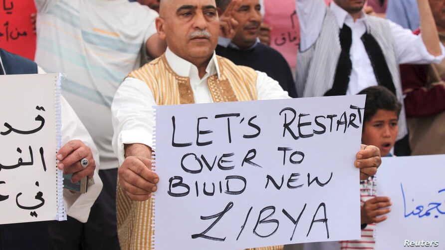Supporters of Libya's unity government hold signs during a demonstration at Martyrs' Square in Tripoli, April 1, 2016.