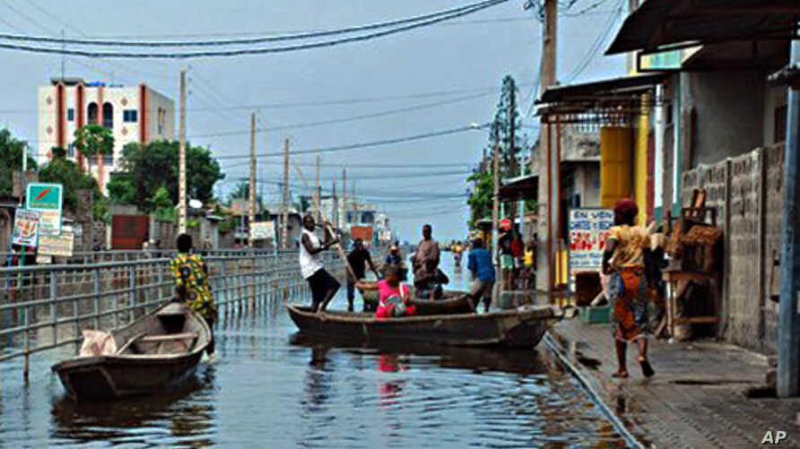 Residents board canoes in a city street flooded by an overflowing drainage canal, in the Saint Martin neighborhood of Cotonou, Benin, 09 Oct. 2010