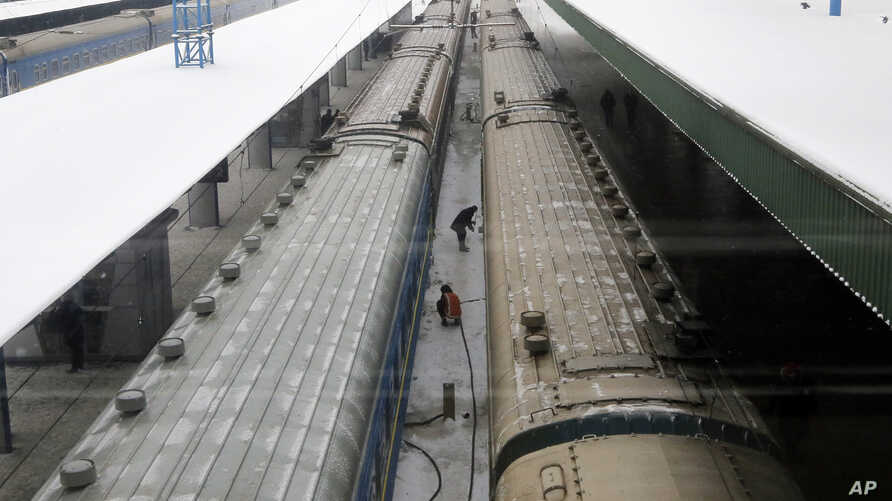 FILE - Railway workers fix trains at the central station in Kiev, Ukraine, Jan.12, 2017.